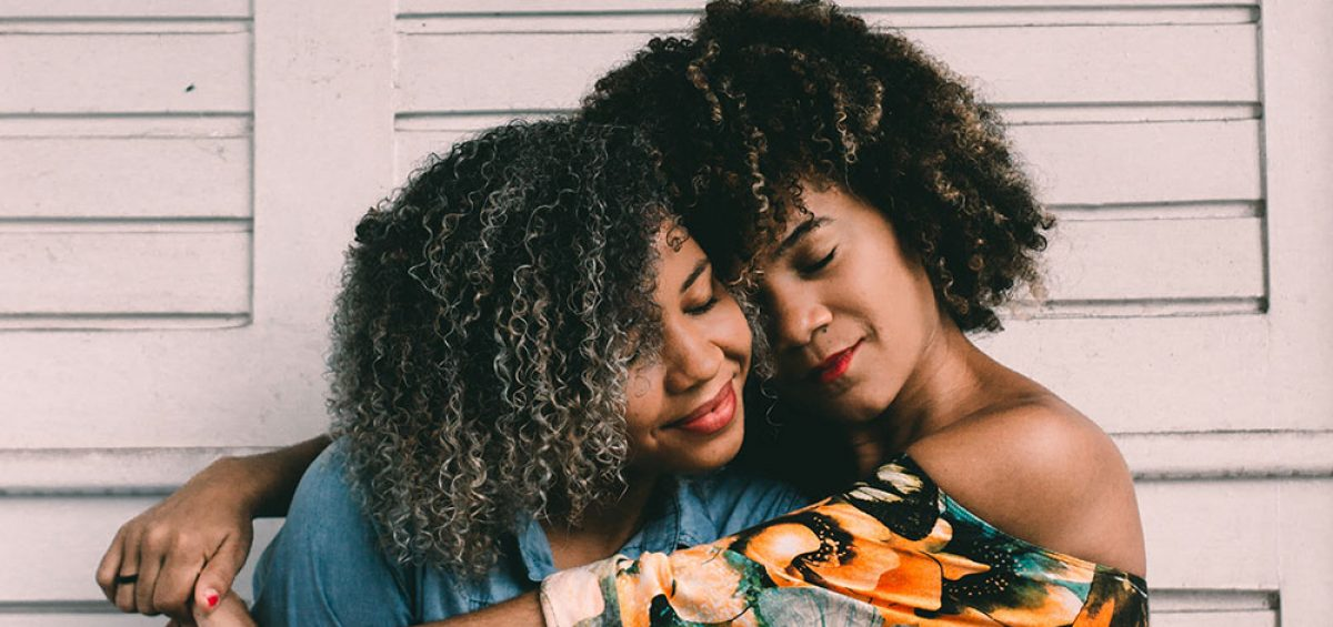 Two caring sisters with dark curly hair hugging - carer support groups