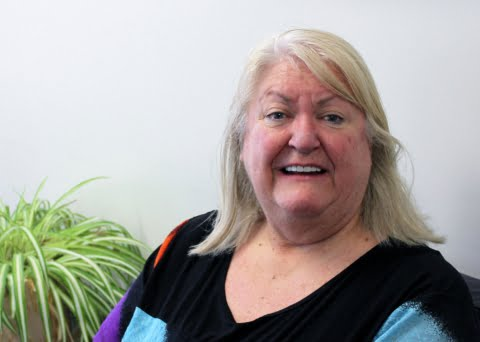 Older woman smiles at the camera in an office area