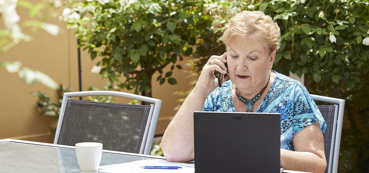 Woman on the phone to Carer Gateway whilst sitting outside