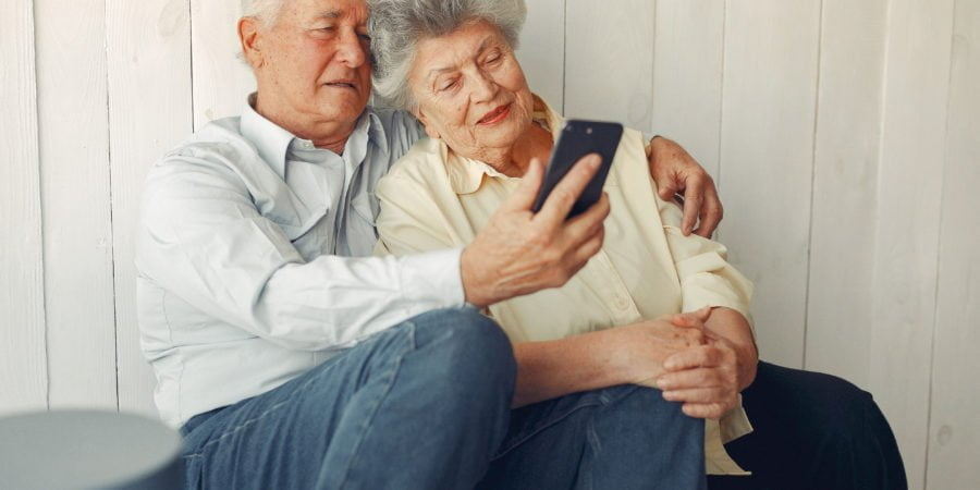 Elegant old couple sitting at home and using a phone