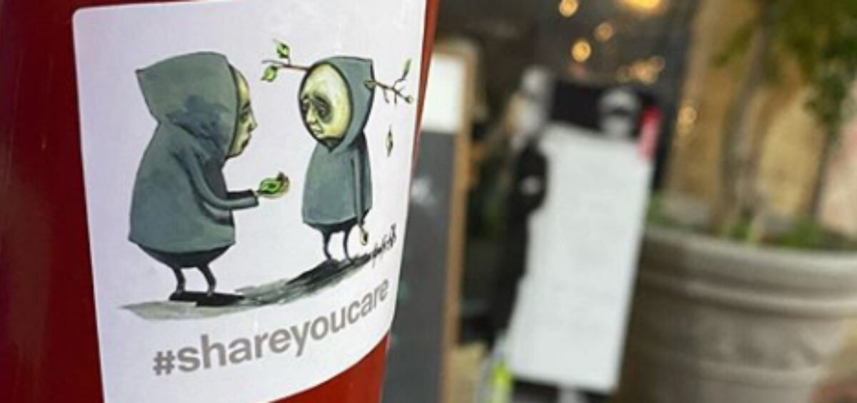 Stormie Mills sticker design of two people in hooded clothing for #ShareYouCare Sticker Project stuck onto a pole