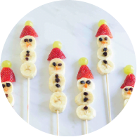 Bananas, strawberries, grapes and raisins on a skewer to form the shape of a snowmen