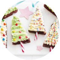 Brownies shaped as Christmas trees, decorated with colourful icing and sprinkles with candy canes.