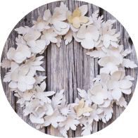 A Christmas wreath made from white cardboard and paper has been placed on a wooden background