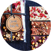 """Small decorated chocolate blocks covered with nuts and dried berries, to the left side there is packaged chocolate with a tag reading """" Choc Bark""""."""
