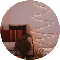 A picture of a room with a chair and Christmas lights have been fixed to the wall to create the shape of a Christmas tree