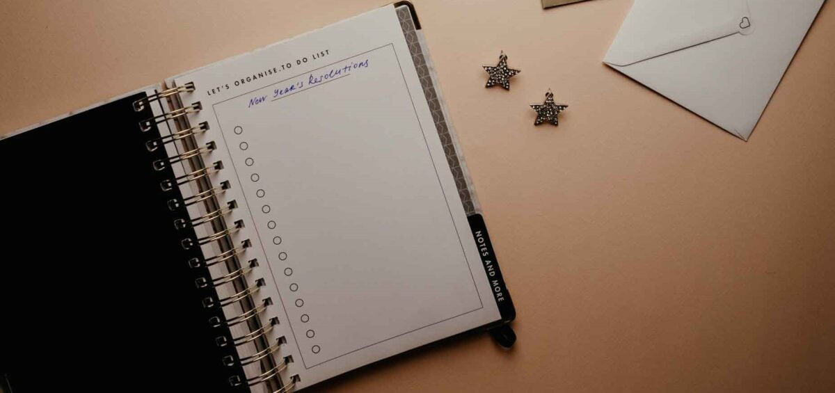 A journal on a desk with the words New Year's Resolutions written at the top of the page.