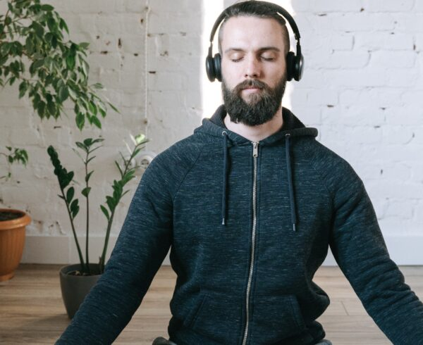 Man sitting and meditating to look after his mental health